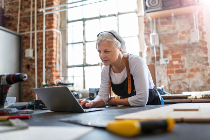 Confident senior woman working in workshop