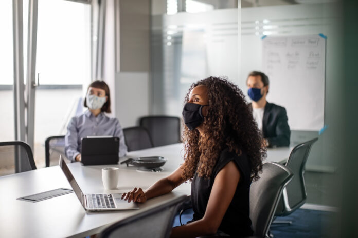 Business people wearing masks in a meeting