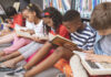 School kids sitting on cushions and studying over books in a library